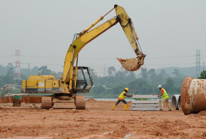 Due muratori che sollevano la lastra di cemento armato facendo uso dell'escavatore fotografie stock