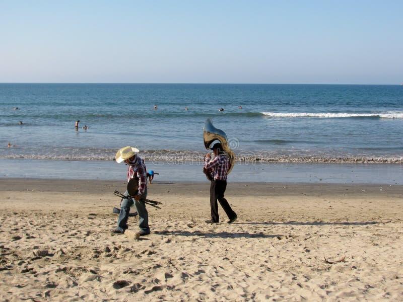 Due musicisti passeggiano sulla spiaggia che porta i loro strumenti fotografie stock