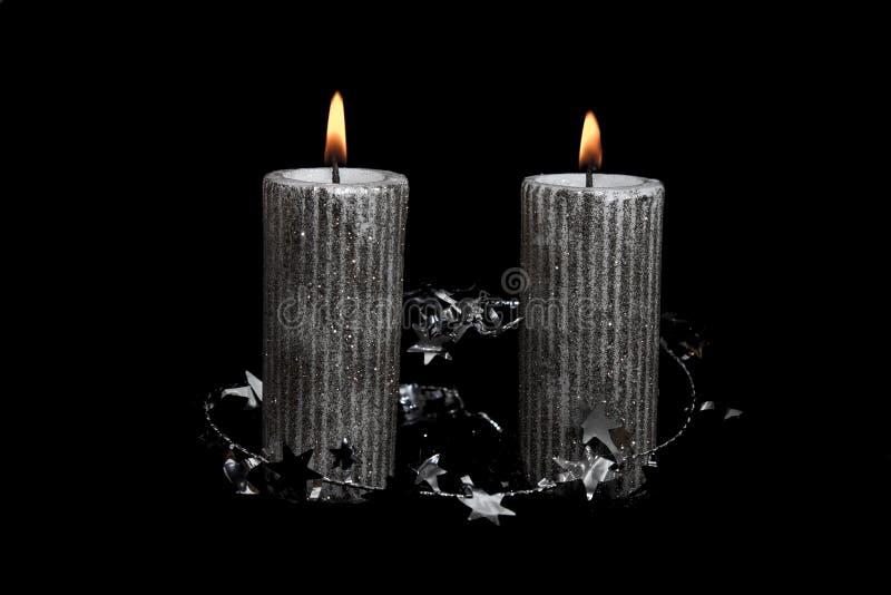 Due Natali argentano le candele sui precedenti neri immagine stock libera da diritti
