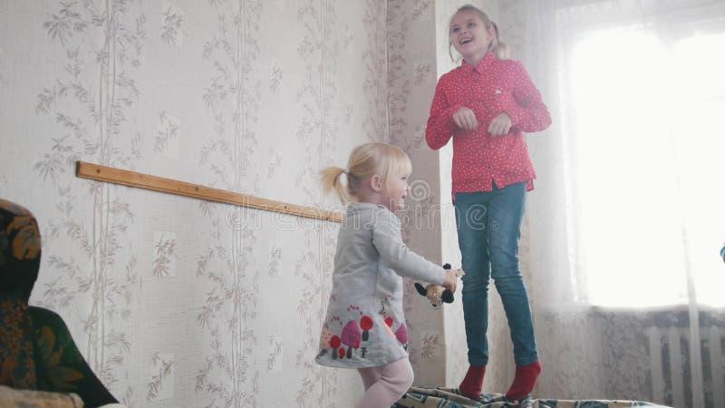 Due neonate sveglie dei bambini che giocano e che si divertono nella stanza dei bambini fotografia stock