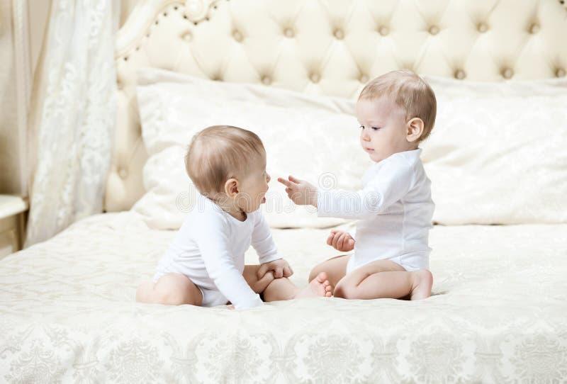 Due neonati che giocano sul letto fotografia stock