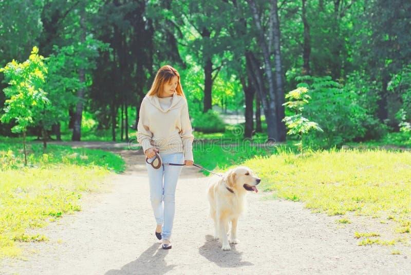 Due?o de la mujer que camina con su perro del golden retriever en el correo en verano fotos de archivo