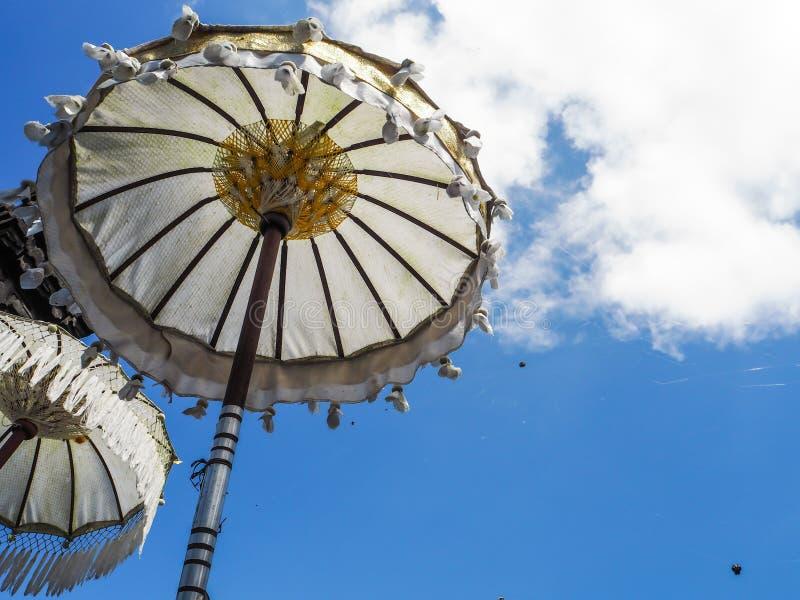 Due ombrelli bianchi di balinese contro un fondo del cielo blu fotografie stock libere da diritti