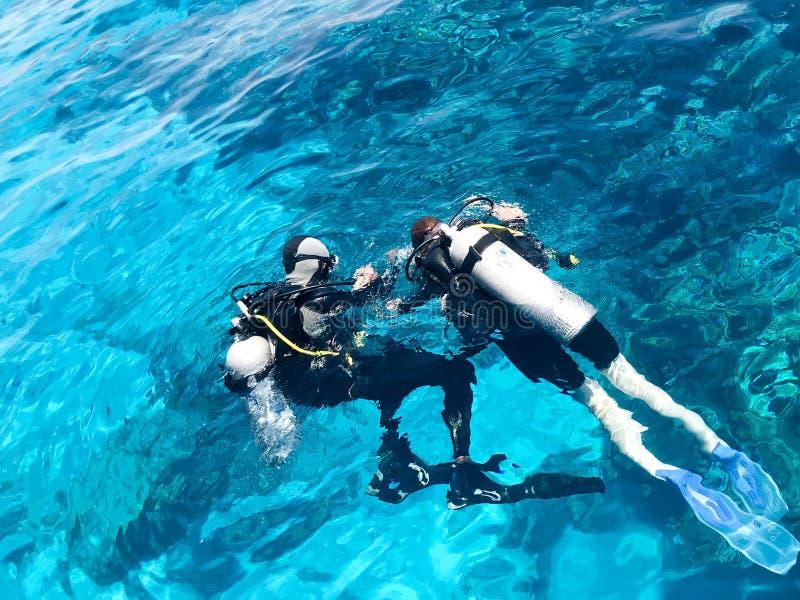 Due operatori subacquei nei vestiti neri di immersione con bombole, in un uomo ed in una donna con le bombole d'ossigeno affondan fotografia stock libera da diritti