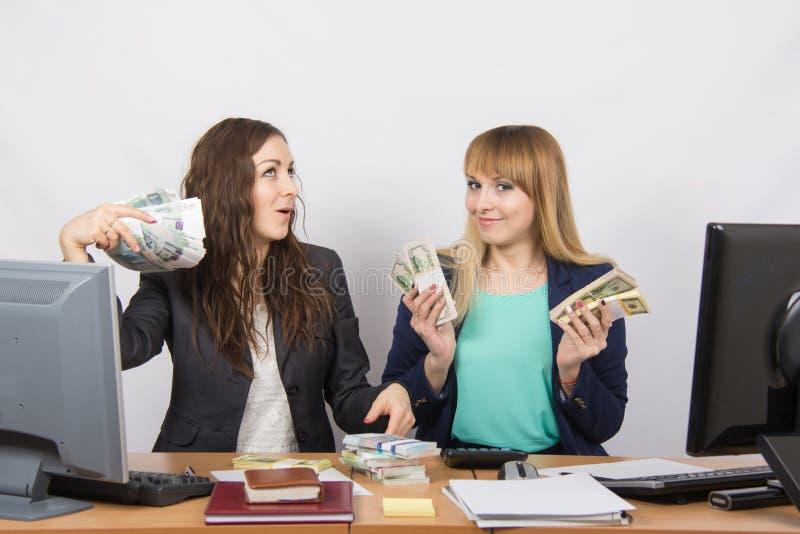 Due pacchi felici dell'ufficio di vanteria delle ragazze di soldi fotografia stock