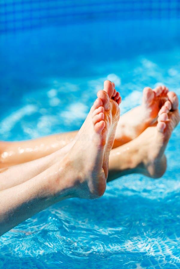 Due paia dei piedi femminili che spruzzano nello stagno, spruzzatura dell'acqua immagini stock