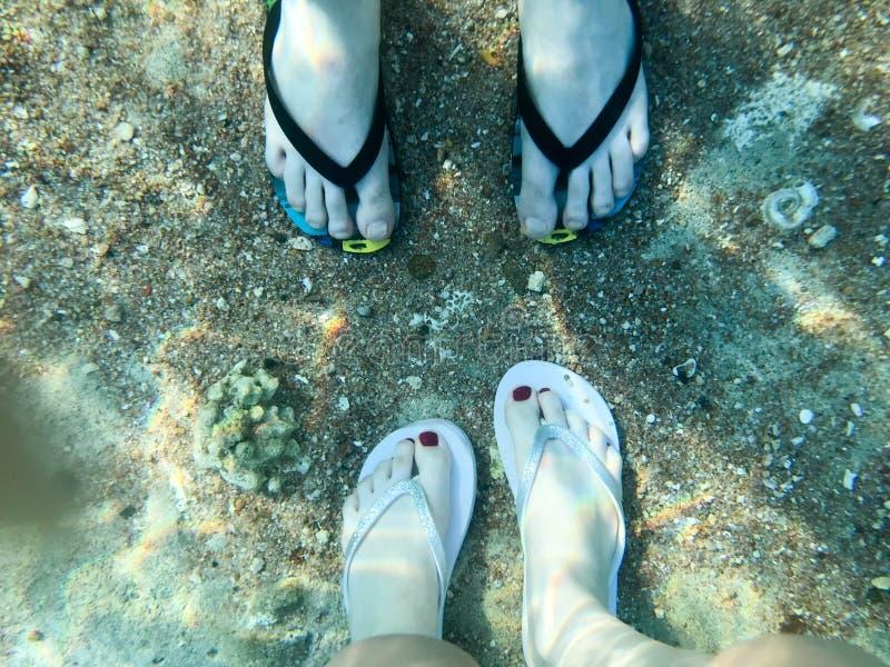 Due paia delle gambe maschii e femminili in pantofole, piedi con le dita nei flip-flop sotto l'acqua, vista subacquea del mare, O immagini stock