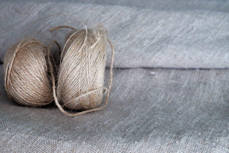 Due palle di cordicella sono su un tessuto di tela ruvido Materiali ed ecologia naturali Fondo grigio fotografia stock libera da diritti