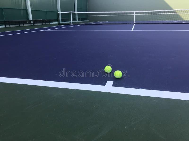 Due palline da tennis verdi messe sul campo da tennis blu con rete su fondo immagine stock libera da diritti