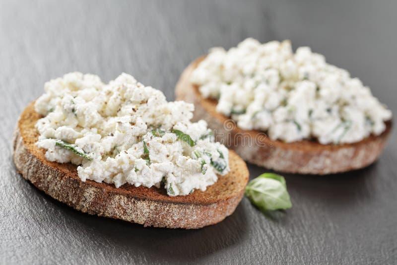 Due panini della segale o panino aperto del bruschettarye con formaggio cremoso e le erbe sull'ardesia fotografie stock libere da diritti