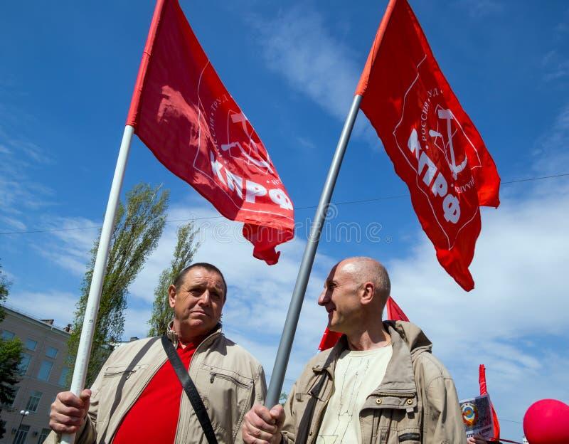 Due partecipanti della dimostrazione di festa dei lavoratori portano le bandiere del partito comunista fotografia stock