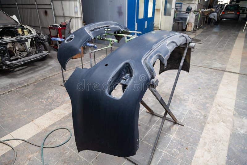 Due parti automatiche dei paraurti sono installate sugli scaffali dopo la verniciatura nell'officina riparazioni dell'automobile  immagine stock