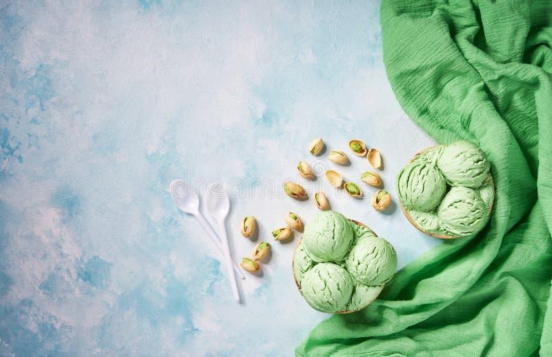 Due parti del pistacchio del gelato in tazza di carta e tovagliolo verde sui colori fondo, vista superiore della menta fotografia stock libera da diritti