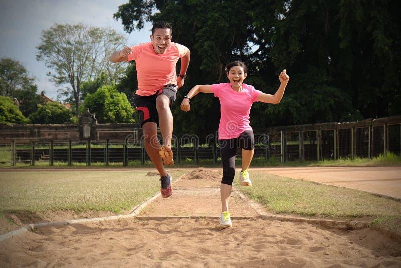 Due partner di sport stanno pareggiando insieme un giorno soleggiato che porta le camice arancio e rosa Se esaminano ed il sorris fotografia stock