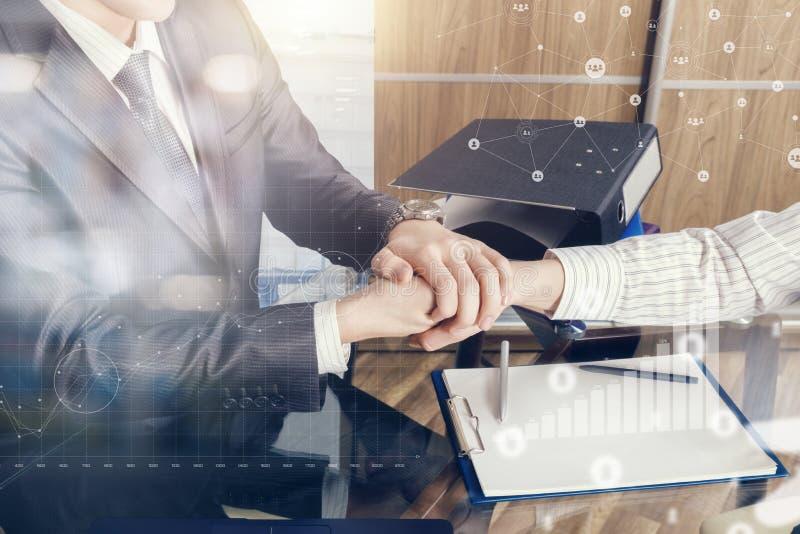 Due partner stanno stringendo le mani all'ufficio che simbolizza il riuscito contratto immagine stock
