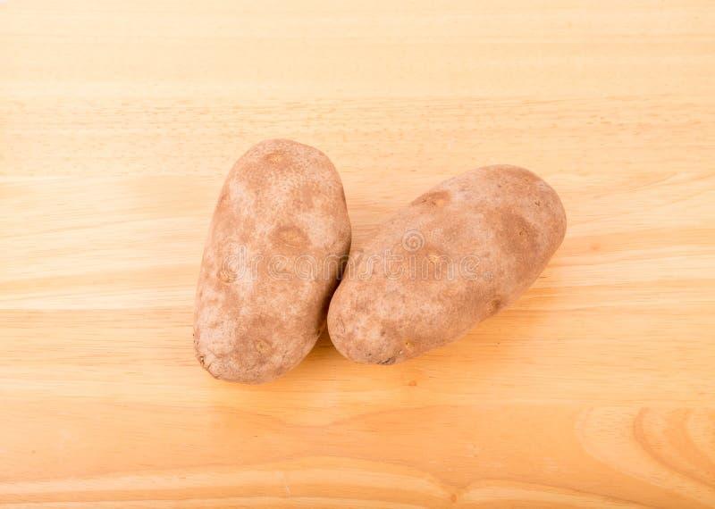 Due patate su una Tabella di legno fotografia stock libera da diritti