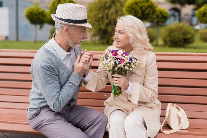 Due pensionati stanno sedendo su un banco nel vicolo Un uomo anziano bacia delicatamente una mano del ` s della donna immagini stock