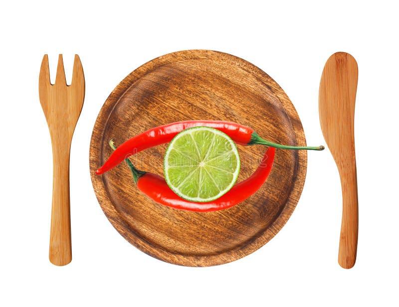 Due peperoncini e fette roventi della calce sul isolat di legno del piatto immagini stock libere da diritti