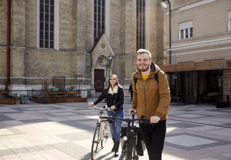 Due persone - amici o coppie, spingenti le loro biciclette in un vecchio quadrato di città in Europa, la Serbia, Novi Sad Sorride fotografia stock libera da diritti