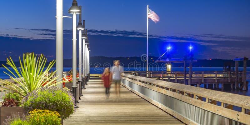 Due persone che camminano sul pilastro di Tacoma al tramonto immagine stock