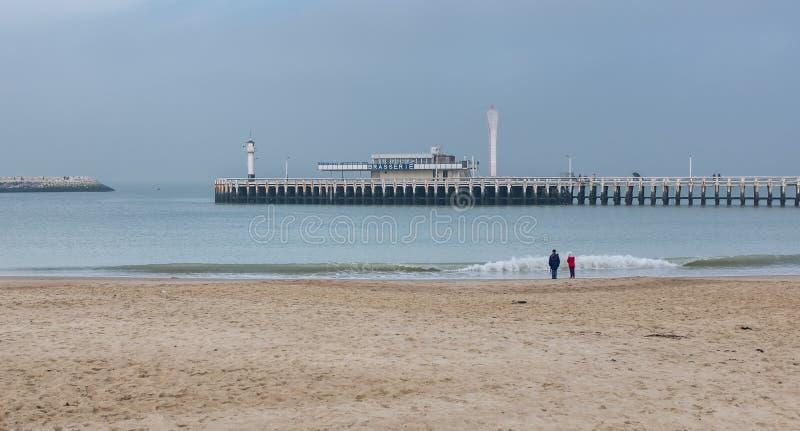 Due persone che godono di una vista sulla spiaggia di Ostenda nel Belgio fotografia stock