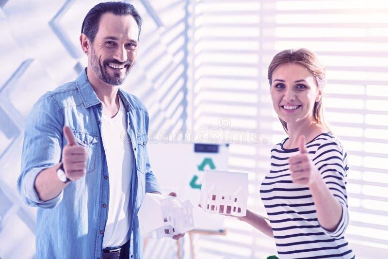 Due persone che sorridono e che mettono i pollici su mentre stando con le piccole case fotografia stock
