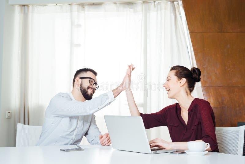 Due persone di affari allegre che celebrano successo e che danno livello cinque immagine stock libera da diritti
