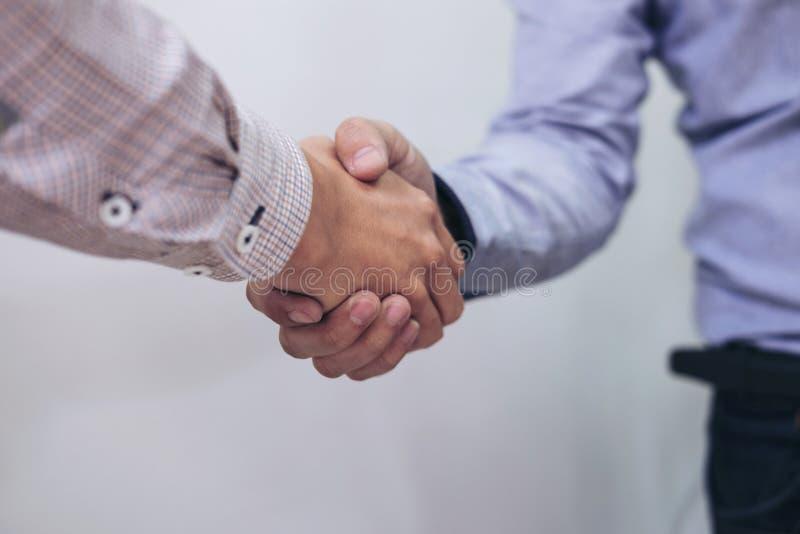Due persone di affari che stringono le mani nel corso di una riunione nell'ufficio, immagine stock