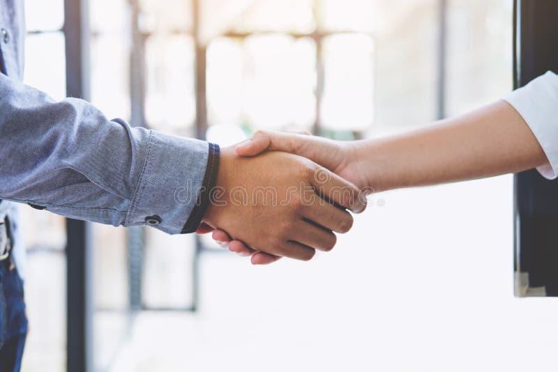Due persone di affari che stringono le mani nel corso di una riunione nell'ufficio, fotografie stock