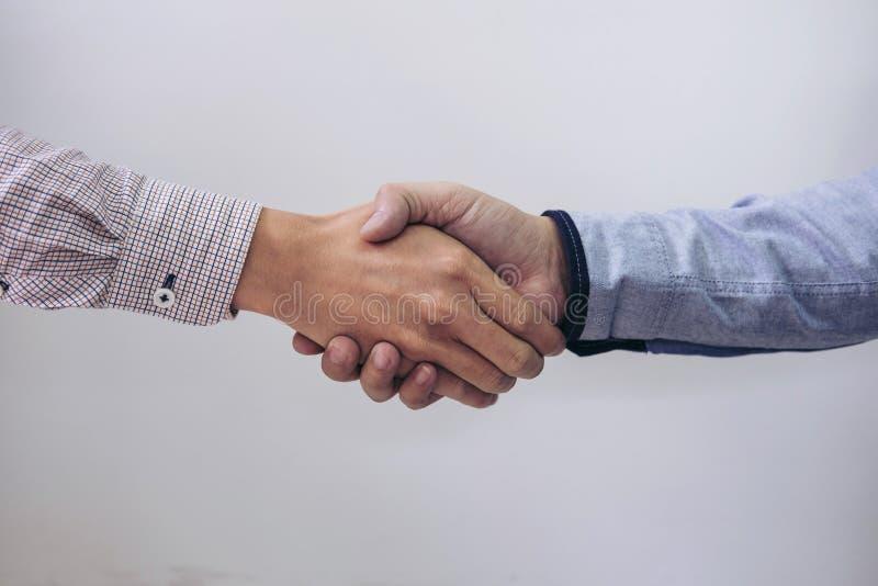 Due persone di affari che stringono le mani nel corso di una riunione nell'ufficio, fotografie stock libere da diritti