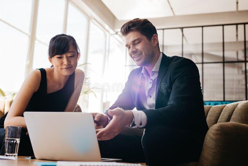 Due persone di affari che utilizzano computer portatile nell'ingresso dell'ufficio moderno fotografia stock libera da diritti