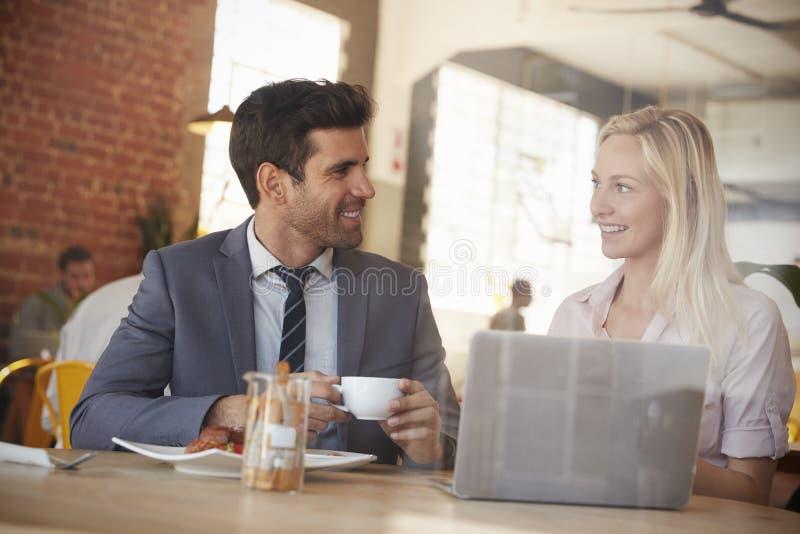 Due persone di affari si incontrano in caffetteria sparata attraverso la finestra immagini stock