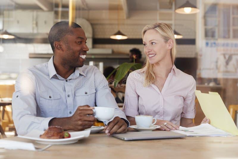 Due persone di affari si incontrano in caffetteria sparata attraverso la finestra immagini stock libere da diritti