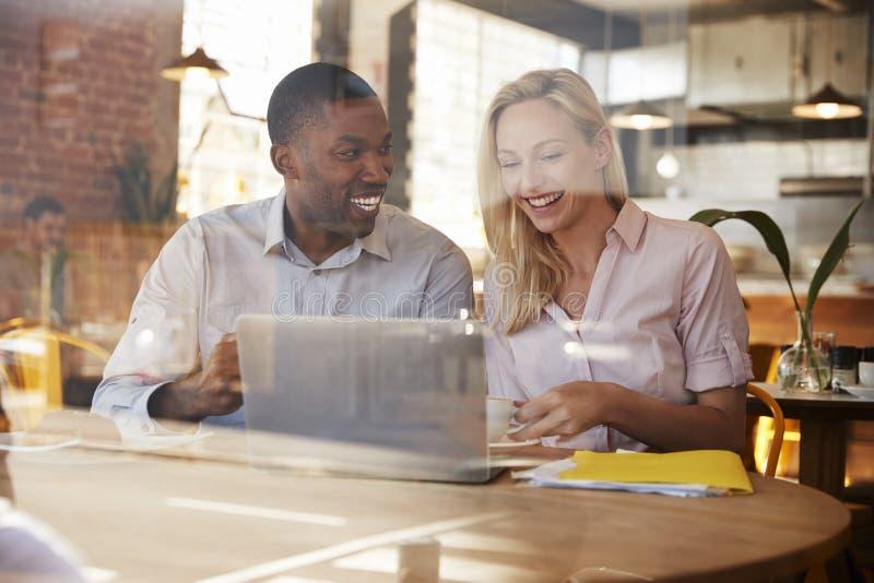 Due persone di affari si incontrano in caffetteria sparata attraverso la finestra fotografie stock libere da diritti
