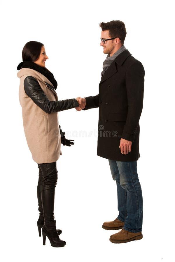 Due persone si sono vestite in cappotto dell'inverno che stringono le mani come segno dei Bu immagini stock libere da diritti