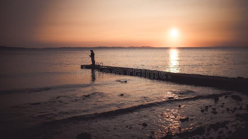 Due pescatori al costo durante il tramonto fotografie stock libere da diritti