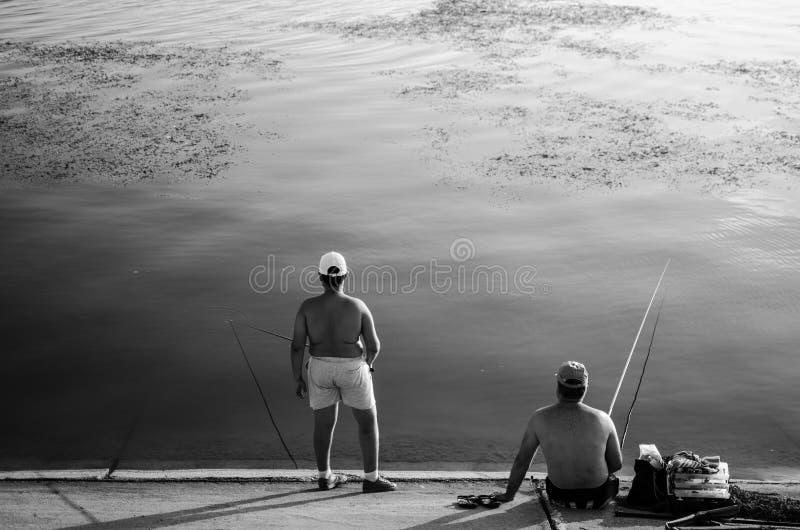 Due pescatori che pescano su un lago immagine stock