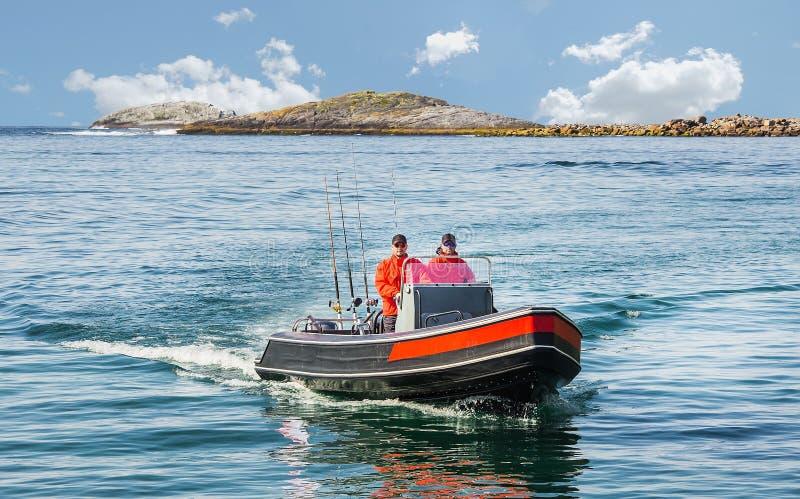 Due pescatori navigano su un'imbarcazione a motore dal mare contro i precedenti fotografia stock libera da diritti