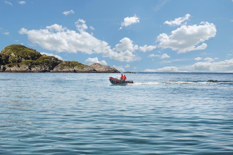 Due pescatori navigano su un'imbarcazione a motore sul mare lungo l'orizzonte fotografie stock