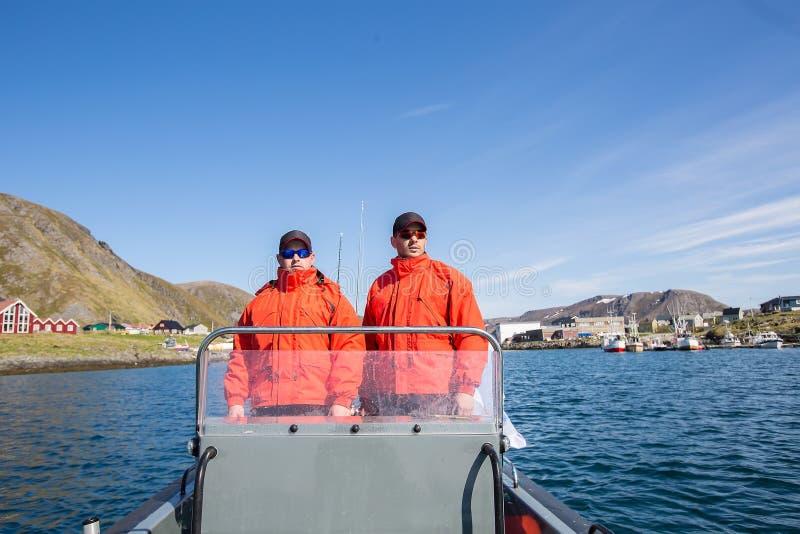 Due pescatori navigano su un'imbarcazione a motore sul mare lungo l'orizzonte immagine stock