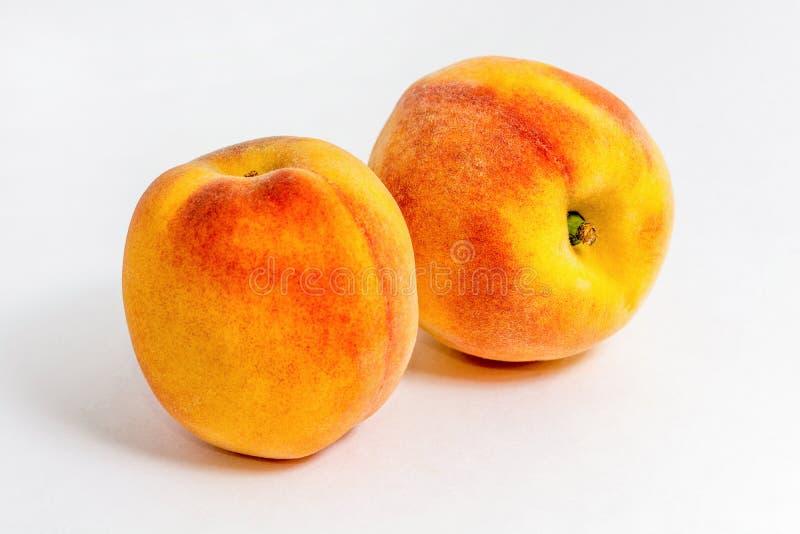 Due pesche sugose Frutti di estate raccolto sull'azienda agricola Igridient delizioso per succo Priorit? bassa bianca immagini stock