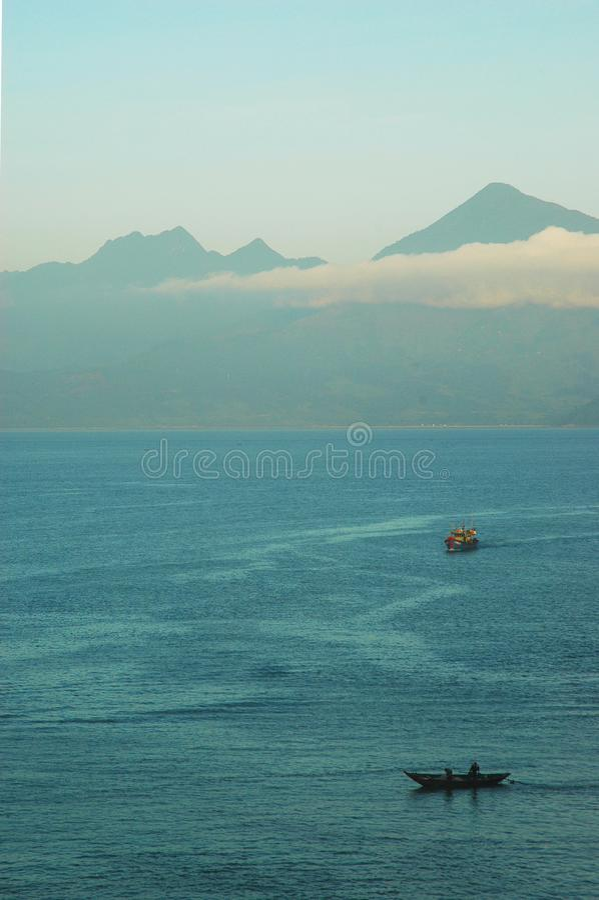 Due pescherecci all'alba su una baia vicino ad una montagna immagini stock