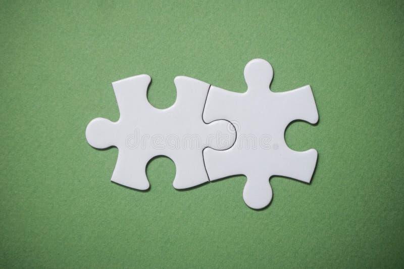Due pezzi collegati del puzzle su fondo verde Il concetto di individuazione delle soluzioni giuste nel lavoro di squadra fotografia stock libera da diritti