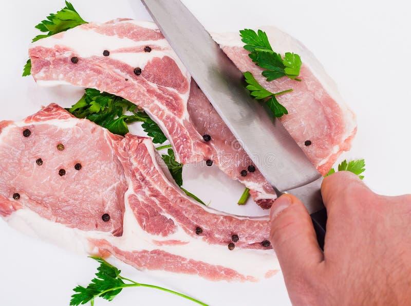 Due pezzi di carne succosi sull'osso con una bugia del pepe su fondo bianco immagini stock