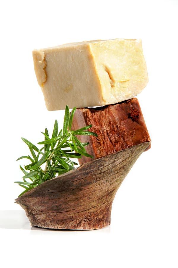 Due pezzi di oliva fatta a mano del cioccolato del caffè e di sapone delle erbe con i rosmarini su di legno isolati su bianco immagini stock
