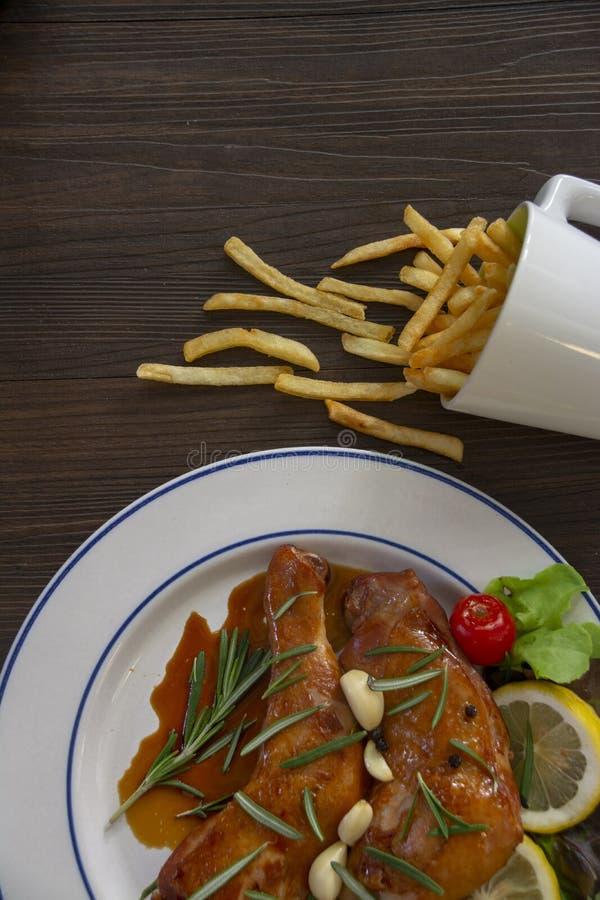 Due pezzi di pollo sono disposti su un piatto bianco e la salsa è versata sul pollo C'è un piatto laterale con le verdure, immagini stock