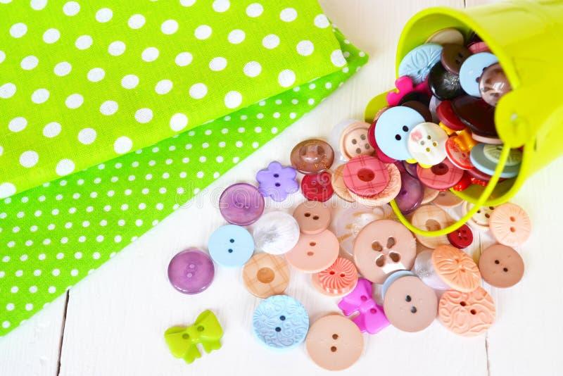 Due pezzi di tessuto verde con il modello di pois, bottoni variopinti messi Priorità bassa di cucito immagine stock