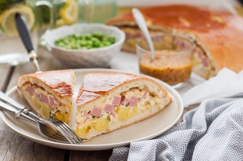 Due pezzi di torta della patata, del prosciutto, della panna acida e del formaggio fotografia stock libera da diritti