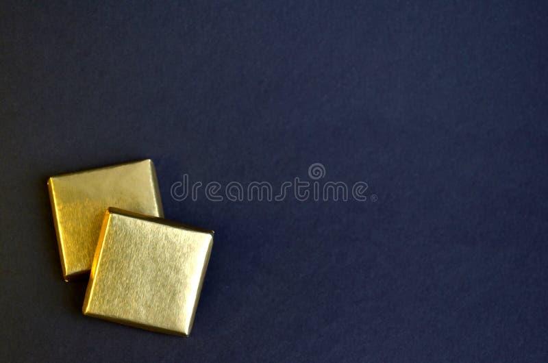 Due pezzi quadrati di cioccolato con stagnola dorata su un fondo blu con copyspace fotografie stock libere da diritti