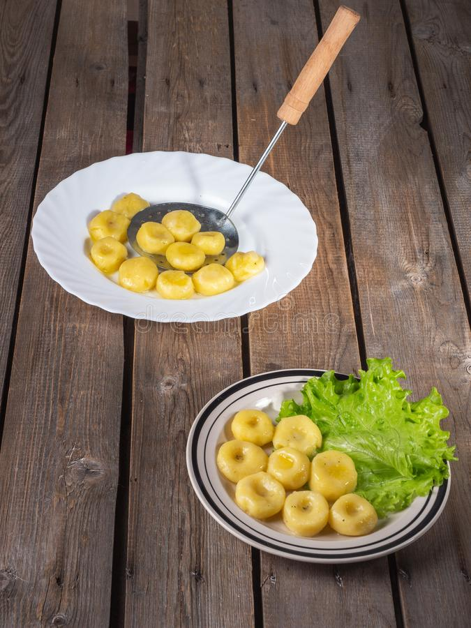 Due piatti degli gnocchi bolliti della patata sulle foglie fresche della lattuga su un piatto ceramico leggero a strisce su una v immagine stock libera da diritti